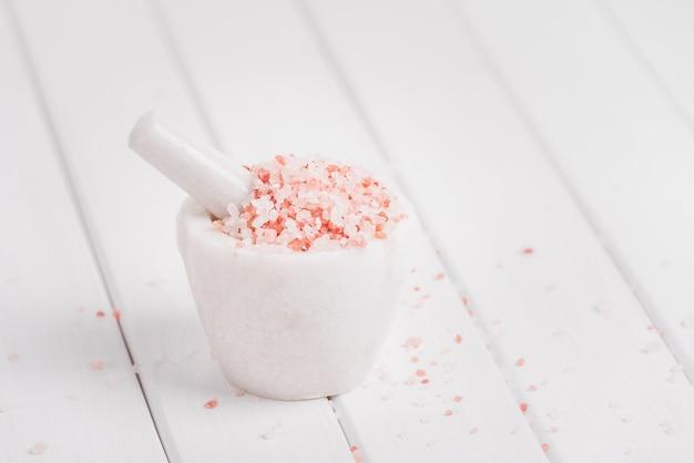 Гималайская розовая соль в белом мраморном ступке на фоне мешка из конопли. гималайская соль обычно используется в кулинарии и в таких продуктах для ванн, как соли для ванн. copyspace.