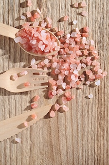 Himalayan pink salt and wooden cutlery on table close up top view