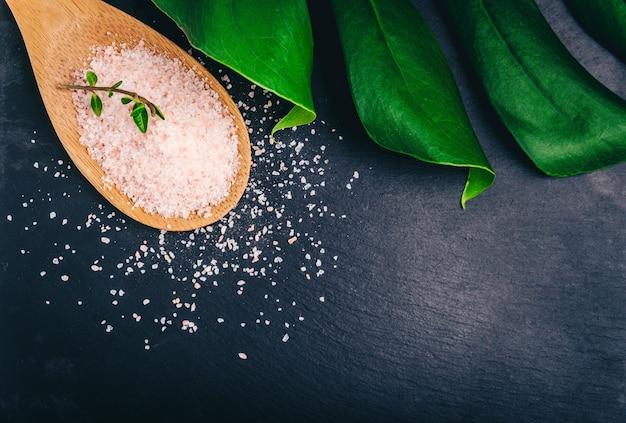 モンステラの葉と黒いスレートプレート上の竹スプーンのヒマラヤ塩。