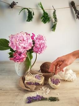 ピンクのアジサイの花瓶の横にあるヴィンテージの木製テーブルの上のヒマラヤの塩のスパイス