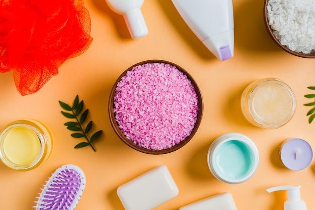 Гималайская соль с косметическими продуктами на цветном фоне