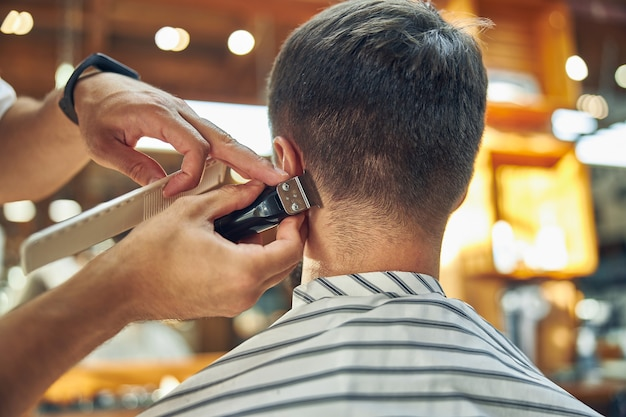 The hindhead of a barbershop client getting his hair cut and trimmed behind his ears