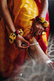 Hindu bride puts traditional bracelet on her leg