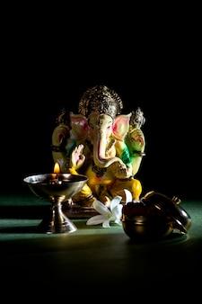 ヒンドゥー教の神ガネーシャ。ガネーシャアイドル。暗い背景にカラフルなガネーシャアイドルの像。テキストまたは見出しのスペース。