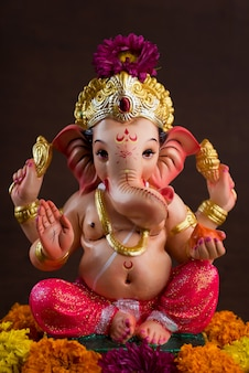 Hindu god ganesha. ganesha idol on dark wooden space.