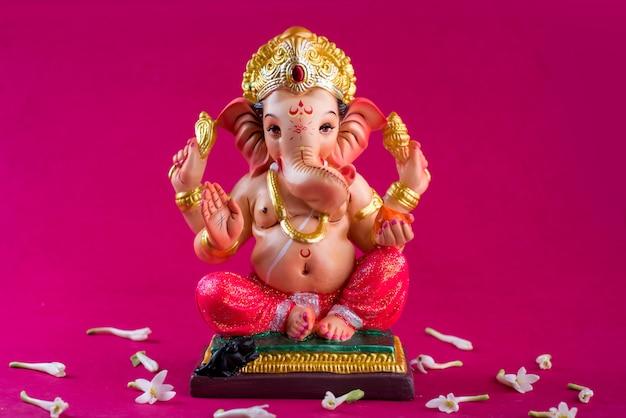 Hindu god ganesha. ganesha idol on pink space.