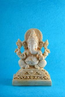 Идол индуистского бога ганеши на синей поверхности
