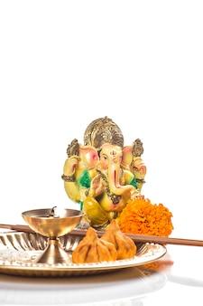 ヒンドゥー教の神ガネーシャ。主ガネーシャの像。白い背景の上の崇拝(プージャ)の配置。