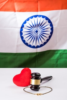 Hindu marriage law concept showing wooden gavel, mangalsutra and red stuffed heart toy, selective focus