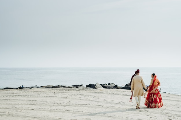 Hindu wedding couple walks along the ocean shore