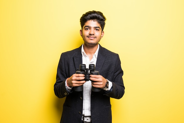 Hindu young man with binoculars isolated on yellow wall