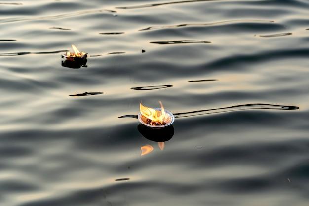 インド、リシケシの神聖なガンジス川の水でヒンドゥー教の宗教儀式プージャの花とキャンドルをクローズアップ