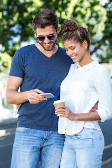 Hip couple looking at smartphone int he city