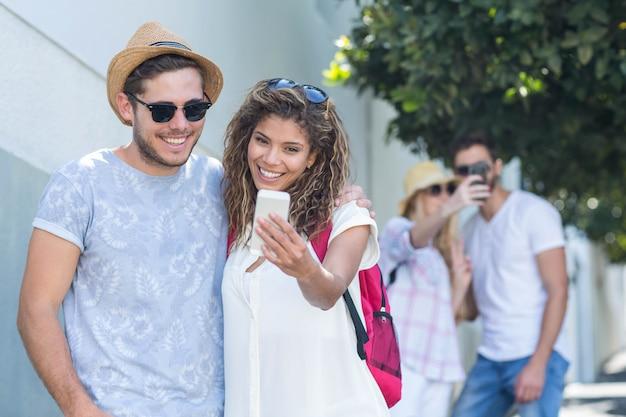 Hip couple taking selfie on the street