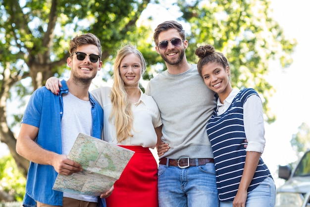 Hip friends holding map and smiling at the camera on the street