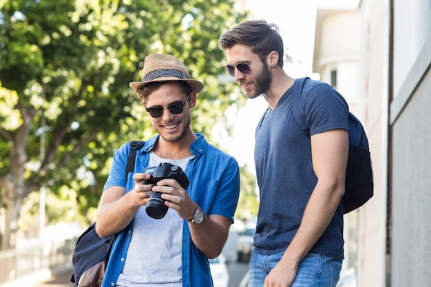 Hip friends looking at digital camera in the streets