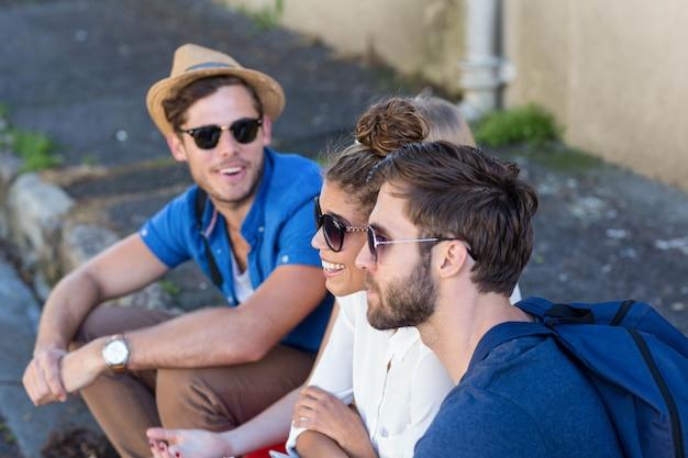 Hip friends sitting on sidewalk in the city