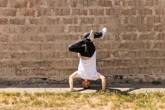 Hip hop acrobatic break dancer dancing against wall