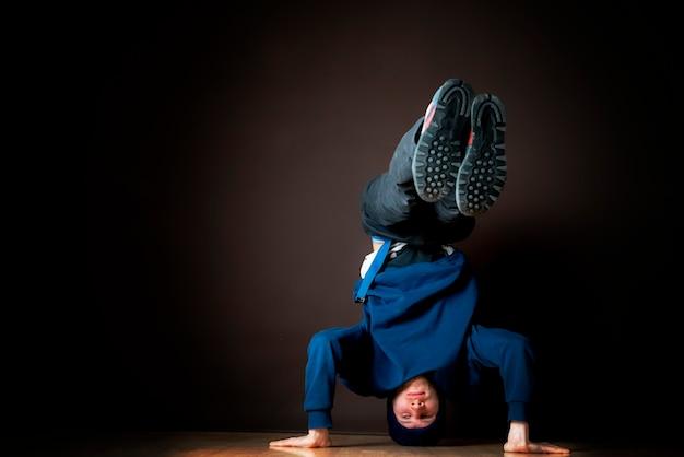 힙합 댄서는 어두운 스튜디오 b에서 거꾸로 머리 스탠드를 수행합니다.