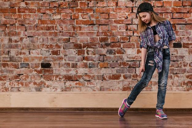 십대를위한 힙합. 도시 스타일. 스튜디오, 벽돌 벽 배경 여유 공간에에서 현대 어린 소녀. 삶을위한 브레이크 댄스, 움직임 개념