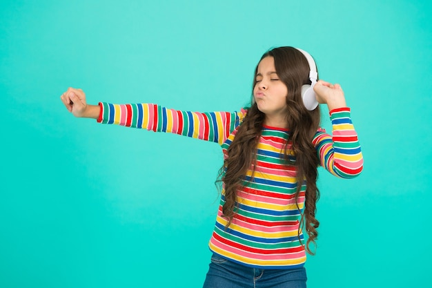 Девушка хип-хопа. маленькая девочка слушает музыку в наушниках. счастливый танцующий ребенок. подросток ребенок выражает позитив. оптимистичная школьница носит яркую одежду. лучшие летние хиты. на положительную мелодию. поймай мою волну.