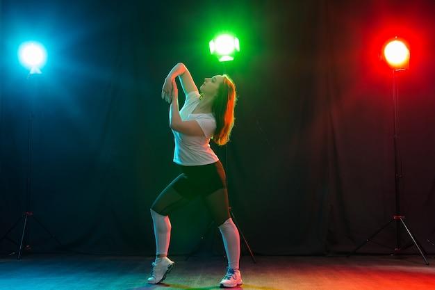 Hip-hop, jazz-funk, tecktonik, waacking, trance and street dances concept - young woman dancing jazz-funk at studio.
