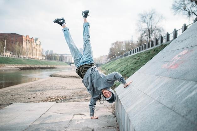 Hip hop performer, upside down motion on the street. modern dance style. male dancer