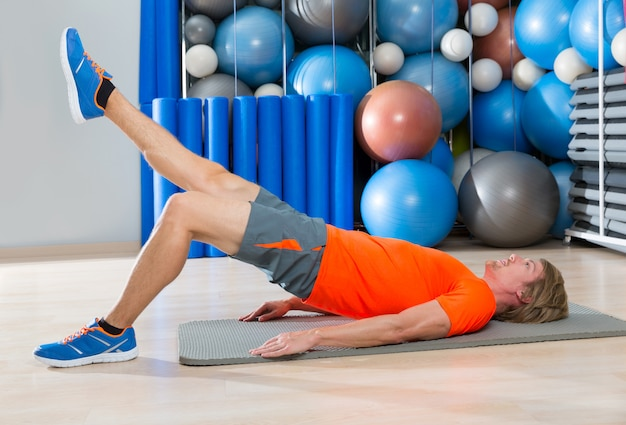 Hip lift with leg extension blond man gym exercise