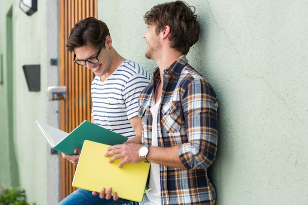 Hip men leaning against wall and holding notebooks on the street