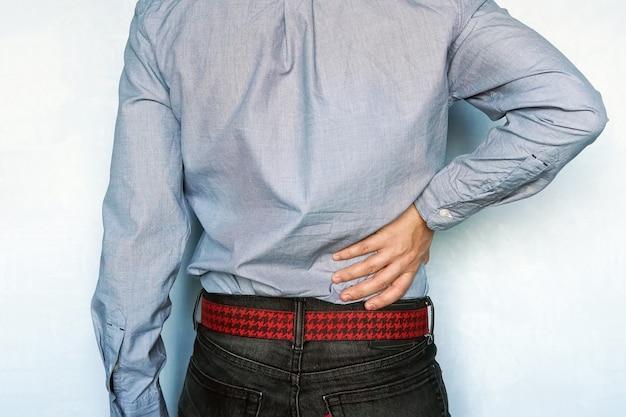 股関節または背中の怪我。若い男が彼の傷ついた体の右側に触れています。肝疾患。男は病気の肝臓を後ろからつかみます。腎臓結石
