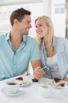 Hip young couple having desert and coffee together