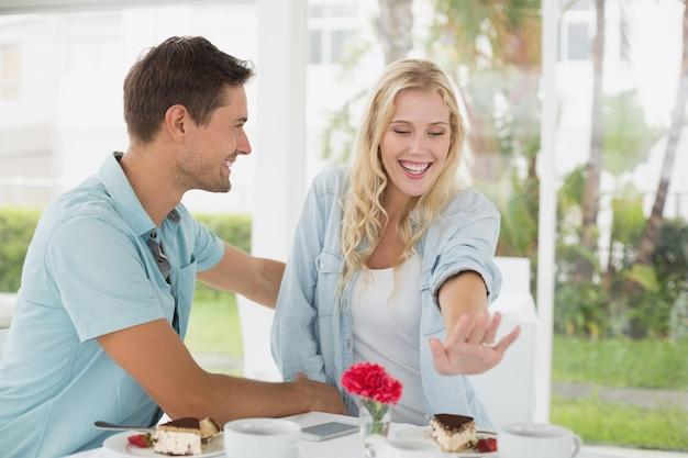 Хип-молодая пара сидит за столом, любуясь обручальное кольцо на террасе кафе в солнечный день