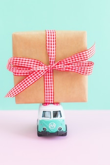Hippie bus with new year christmas present on the roof miniature small car banner party theme