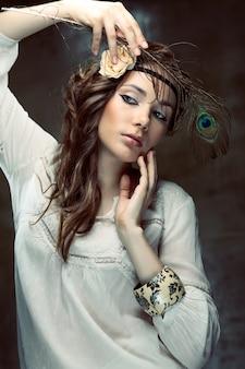 グランジの背景に孔雀の羽でポーズをとってヒッピーの女の子