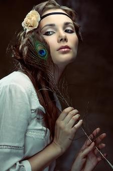 孔雀の羽でポーズをとるヒッピーの女の子