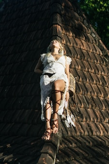 Hippie girl with long blond hair in a dress on the roof.