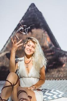 지붕에 드레스에 긴 금발 머리를 가진 히피 소녀.