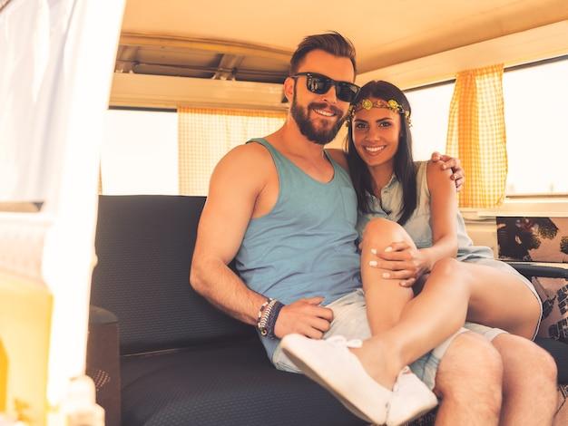 Любовь хиппи. счастливая молодая пара, обнимая друг друга и улыбаясь, сидя на задних сиденьях своего минивэна