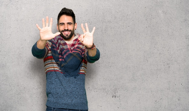 Hippie man counting eight with fingers over textured wall