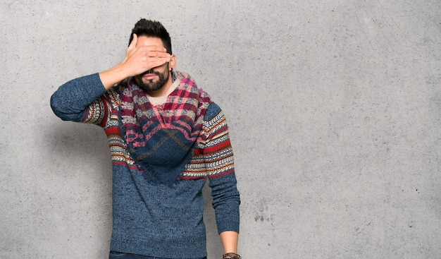 Hippie man covering eyes by hands. do not want to see something over textured wall
