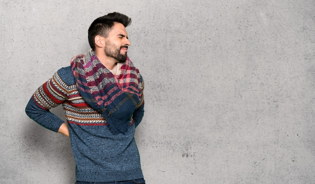Hippie man suffering from backache for having made an effort over textured wall