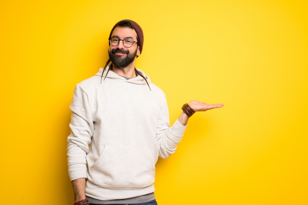 Hippie man with dreadlocks holding copyspace imaginary on the palm to insert an ad