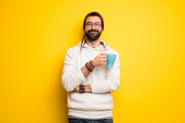 Hippie man with dreadlocks holding a hot cup of coffee