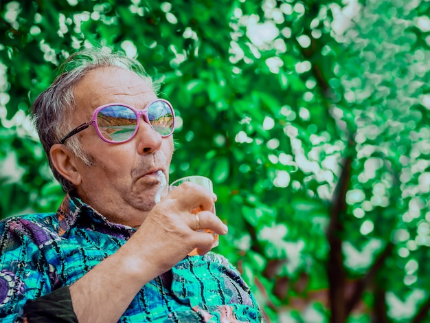 Hippie old man with a glass of alcohol enjoying life