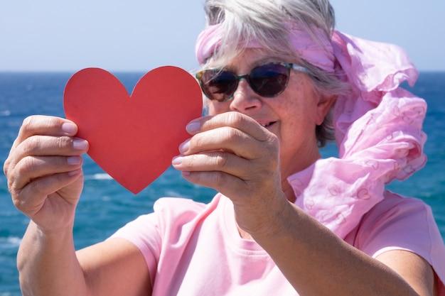 ハート型の紙を保持しているサングラスとピンクのフラールを持つヒッピーの年配の女性。海で風の強い日、自然の概念への愛