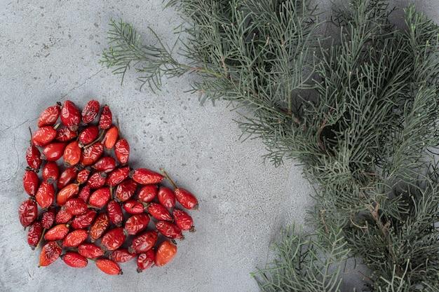 I fianchi si raggruppano a forma di cuore accanto a rami di pino su una superficie di marmo