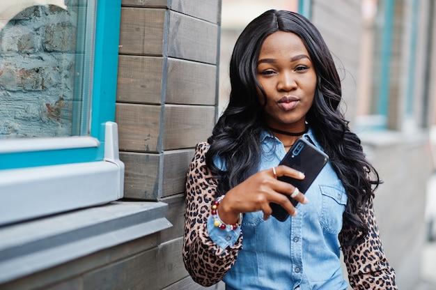 힙스터 아프리카계 미국인 소녀는 표범 소매가 달린 청바지 셔츠를 입고 휴대전화를 손에 들고 거리에서 창문이 있는 목조 주택을 배경으로 포즈를 취합니다.