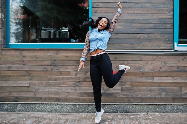Hipster african american girl wearing jeans shirt with leopard sleeves jump at street against wooden house with windows.