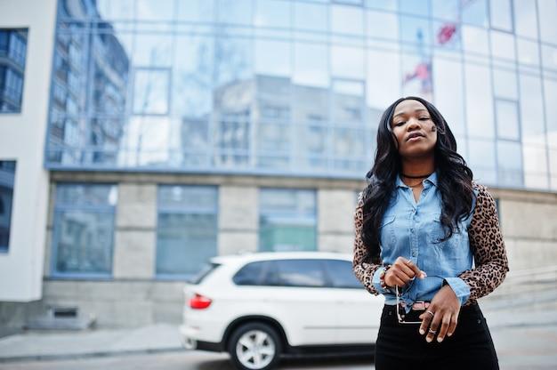 青い窓と白いsuv車のあるモダンなオフィスビルに対して通りでポーズをとるヒョウの袖のジーンズシャツを着ている流行に敏感なアフリカ系アメリカ人の女の子。