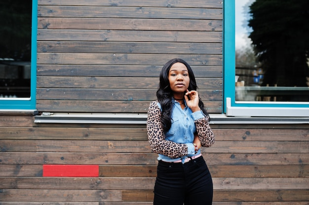 Hipster african american girl wearing jeans shirt with leopard sleeves posing at street against wooden house with windows.